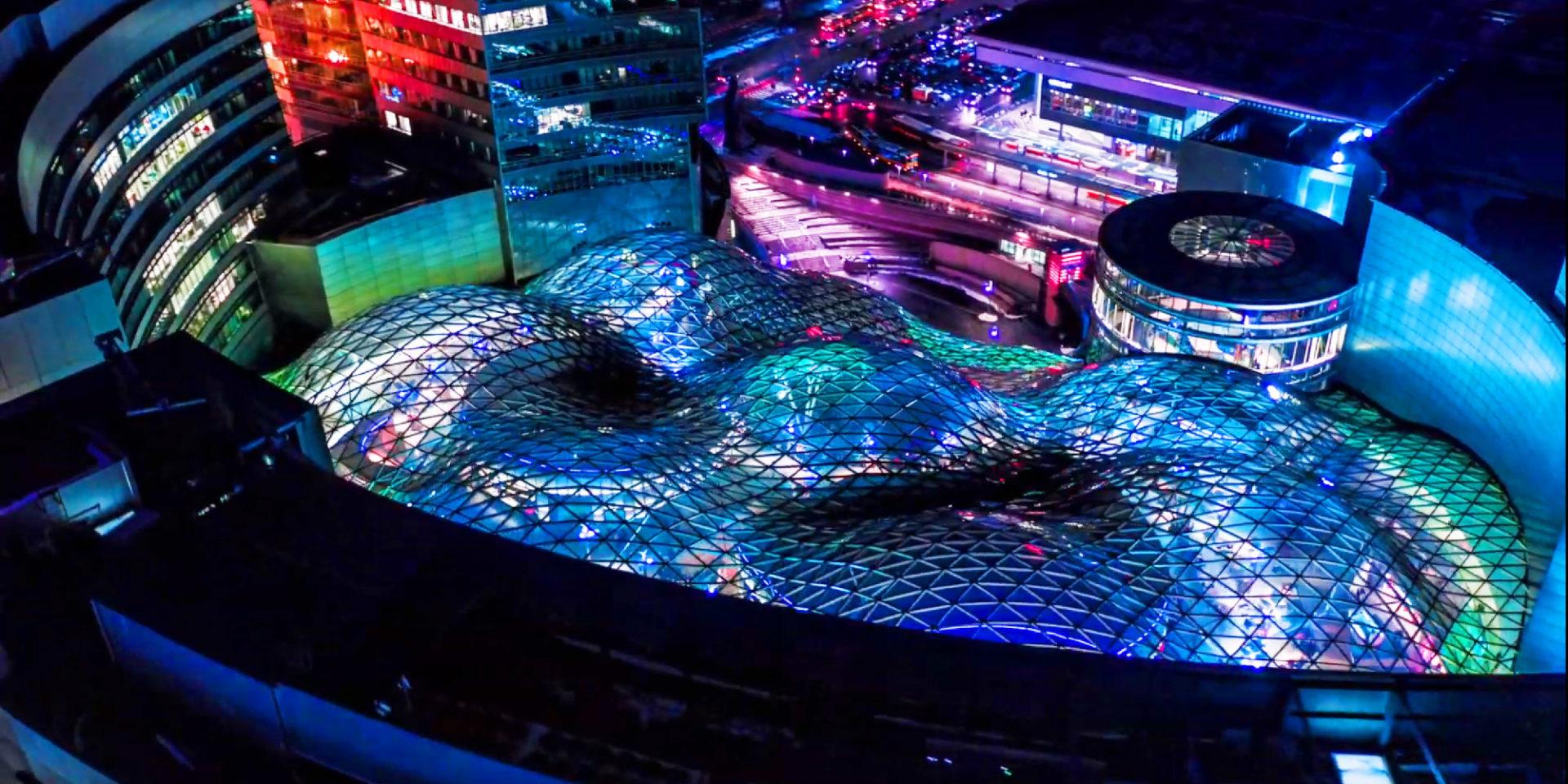 Widok na Złote Tarasy z góry, przeszklona konstrukcja zaokrąglonych kopuł podświetlona jest na niebiesko, wyraźnie widać trójkątną teksturę kopuł